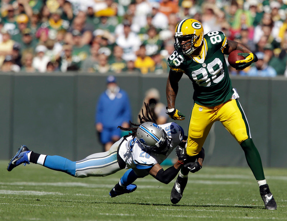 . Detroit Lions\' Louis Delmas (26) tries to stop Green Bay Packers\' Jermichael Finley (88) after a catch during the first half of an NFL football game Sunday, Oct. 6, 2013, in Green Bay, Wis. (AP Photo/Jeffrey Phelps)
