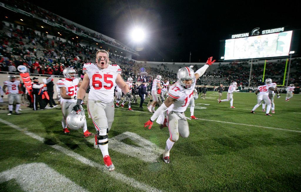 . Ohio State players, including Pat Elfein (65) and Jalin Marshall (17) celebrate as time expires in the team\'s 49-37 win over Michigan State in an NCAA college football game, Saturday, Nov. 8, 2014, in East Lansing, Mich. (AP Photo/Al Goldis)