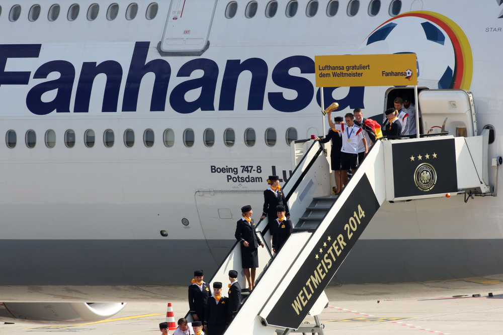 """. Germany\'s defender Philipp Lahm of the German national football team gets off the airplane, a Lufthansa jet rebranded \""""Fanhansa\"""", at Berlin airport Tegel on July 15, 2014, as they arrive from Brazil after they won the FIFA World Cup 2014. The team comes to Berlin for a victory parade at landmark Brandenburg Gate to celebrate their fourth World Cup title, after their 1-0 win over Argentina on July 13, 2014 in Rio de Janeiro in the FIFA World Cup Brazil final game. (ADAM BERRY/AFP/Getty Images)"""