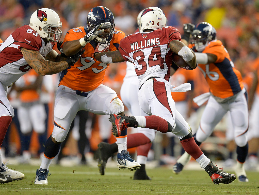 . Arizona Cardinals running back Ryan Williams (34) stiff arms Denver Broncos defensive end Jeremy Beal (93) during the first half on August 29, 2013 at Sports Authority Field at Mile High. The Denver Broncos hosted the Arizona Cardinals in the final game of the preseason. (Photo by John Leyba/The Denver Post)