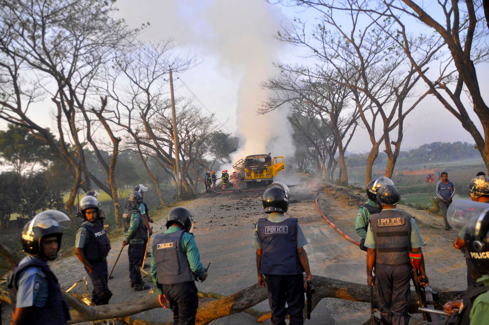 . Bangladeshi firefighters douse the fire on a vehicle set ablaze by activists of the country\'s largest Islamic party Jamaat-e-Islami during clashes with police in Rajshahi, Bangladesh, Sunday, March 3, 2013. Authorities deployed soldiers in a northern Bangladeshi district on Sunday after Islamic party activists clashed with police, leaving five people dead during a nationwide general strike called to denounce war crimes trials. (AP Photo)