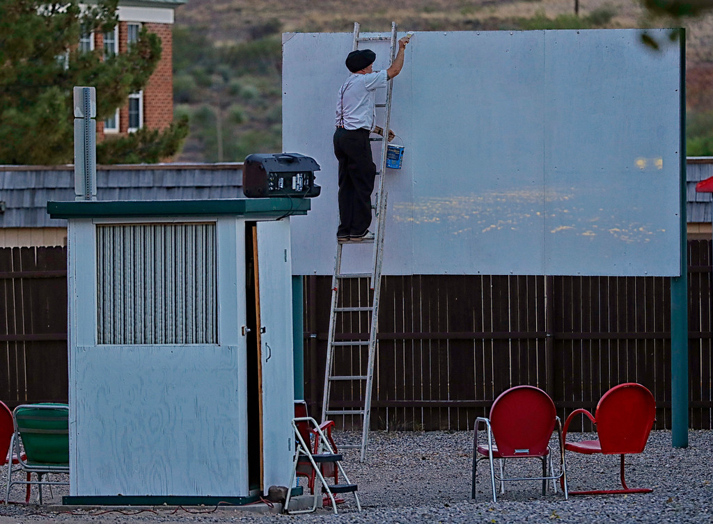 . Manager Brad Hardy applies touch up paint to the big screen at the Shady Dell Trailer Court, Tuesday, April 25, 2017, in Bisbee, Ariz. Movies and advertisements from the 1950\'s are projected nightly. Vintage golf carts and automobile bench seats are used from some of the seating. (AP Photo/Matt York)