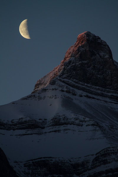 A half moon floats over snow and ice covered, mostly frozen rock, peaks of the Canadian Rockies as seen from Canmore, Alberta, Canada