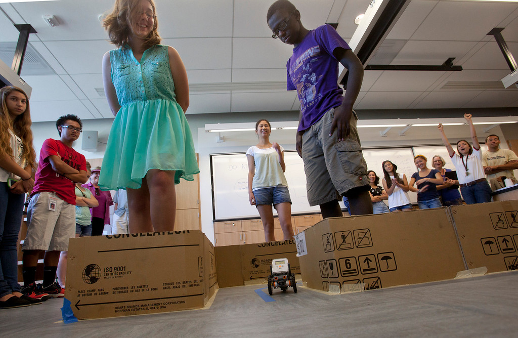 . From left, Kelly Stangl, 15, Olivia Chang, 17, and Elijah Brown, 15, watch as the robot they helped build makes its way through a maze during a summer camp Thursday, July 18, 2013, at Foothill College in Los Altos Hills. The camp is aimed towards underrepresented minorities in STEM: racial minorities, low socioeconomic status, and women. (Patrick Tehan/Staff)