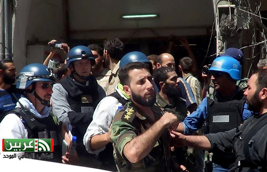 . In this citizen journalism Wednesday, Aug. 28, 2013, file image provided by the United Media office of Arbeen, which has been authenticated based on its contents and other AP reporting, members of a chemical weapons investigation team with blue helmets speak with Syrian rebels in Damascus\' countryside of Zamalka, Syria. The Organization for the Prohibition of Chemical Weapons won the Nobel Peace Prize on Friday, Oct. 11, 2013, for working to eliminate the scourge that has haunted generations from World War I to the battlefields of Syria. (AP Photo/United Media office of Arbeen, File)