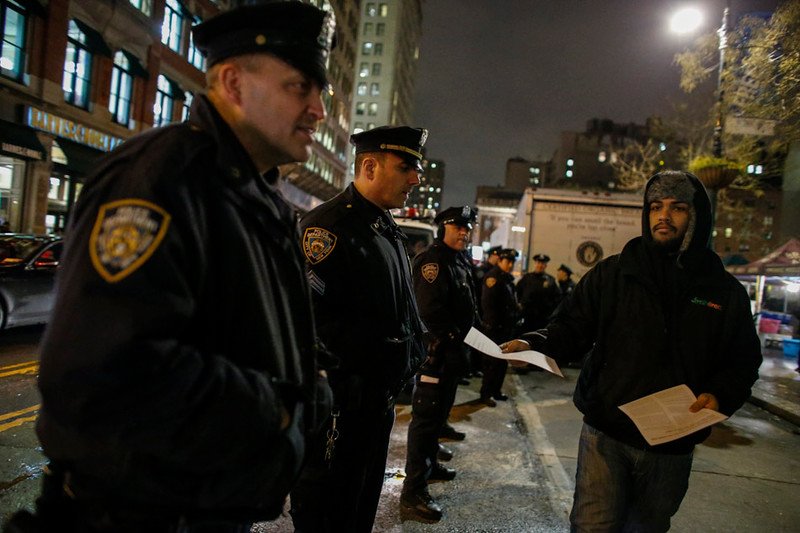 . NEW YORK, NY - DECEMBER 3: A man distributes flyers to police officers as he takes part during a protest in support of Eric Garner at Union Square on December 3, 2014 in New York City. Garner died after being put in a chokehold during an alteration with NYPD officers in the Staten Island borough of New York City. (Photo by Kena Betancur/Getty Images)