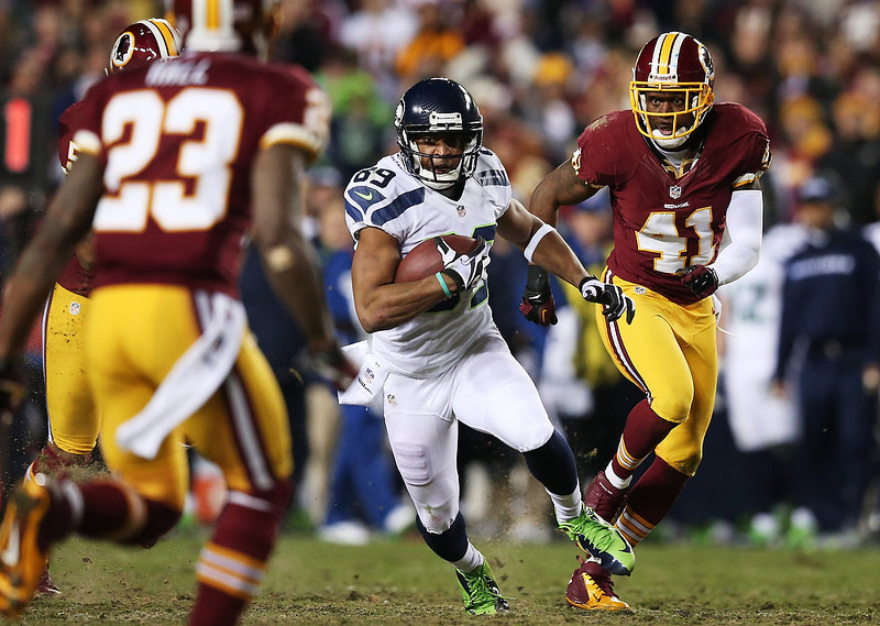 . Clinton McDonald #69 of the Seattle Seahawks carries the ball against the defense of  Madieu Williams #41 and  DeAngelo Hall #23 of the Washington Redskins during the NFC Wild Card Playoff Game at FedExField on January 6, 2013 in Landover, Maryland.  (Photo by Win McNamee/Getty Images)