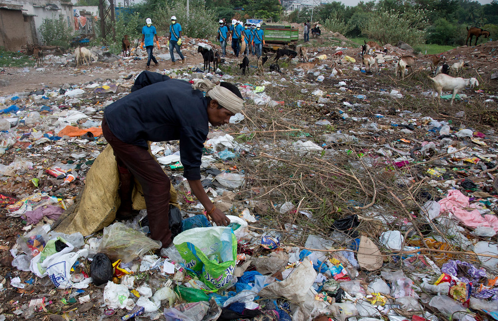 ". A man collects plastic from a garbage pile as members of the National Green Corp clean along the Musi river in Hyderabad, India, Sunday, June 3, 2018. India is the global host for the forthcoming environmental day celebrations on June 5, 2018, with a theme ""Beat Plastic Pollution\"" and launched an awareness program on environmental protection. (AP Photo/Mahesh Kumar A.)"