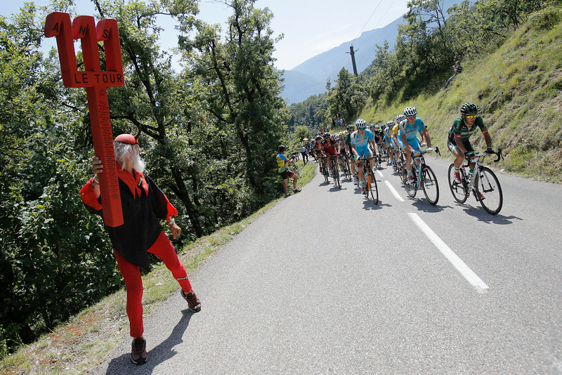 """. Dieter \""""Didi\"""" Senft of Germany, known as El Diablo, left, encourages the pack led by Japan\'s Yukiya Arashiro, right, as it climbs Palaquit pass during the thirteenth stage of the Tour de France cycling race over 197.5 kilometers (122.7 miles) with start in Saint-Etienne and finish in Chamrousse, France, Friday, July 18, 2014. (AP Photo/Christophe Ena)"""