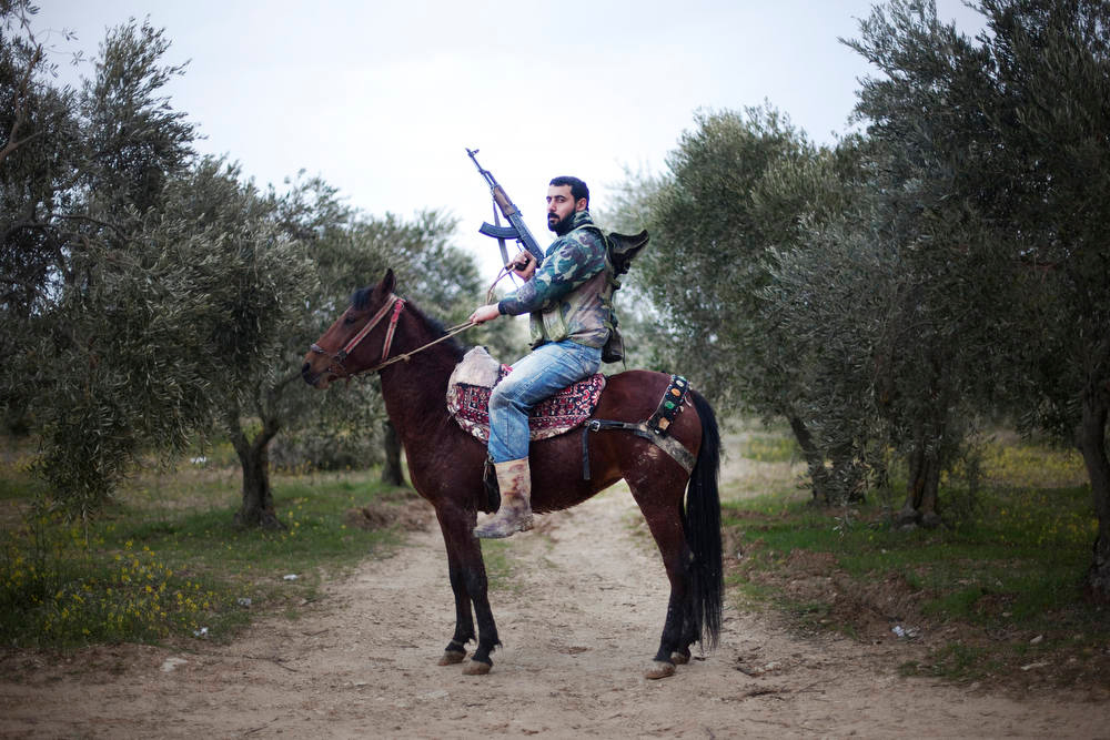 Description of . A portrait of a Free Syrian Army rebel mounted of his steed in Al-Shatouria village near to the Turkish border in northwestern Syria, on March 16, 2012, a year after a revolt against President Bashar al-Assad's regime erupted. AFP PHOTO/GIOGOS Moutafis/AFP/Getty Images