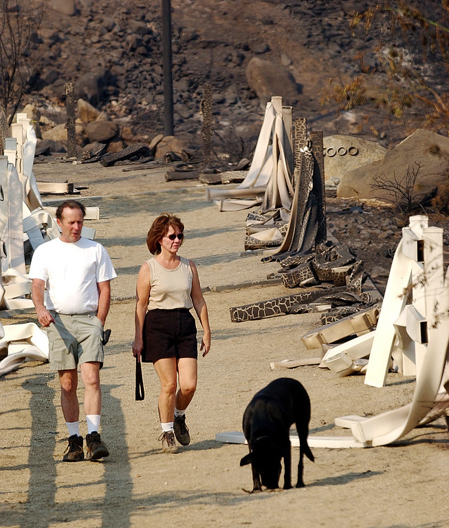". The GrandPrix fire started three days before the Old Fire.  It fed into the Old Fire. Ten years later, there are rumblings that it too was started by an arsonist. But to this day, its origins remain a mystery. Henry and Lisa Harris walk their dog ""Kady\"" down the burned and melted bridal path along Skyline Road in Rancho Cucamonga Monday afternoon October 27, 2003. (Staff photo by Will Lester/Inland Valley Daily Bulletin)"