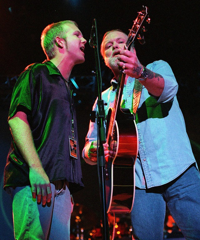 """. Lead singer for the Allman Brothers Gregg Allman, right, sings with his son Devon Allman, 26, during the \""""NASCAR Rocks on the Road with The Allman Brothers 30th Anniversary Tour\"""" at the Greek Theatre in Los Angeles, Saturday, July 31, 1999. The 30-city tour combines rock-n-roll and cars. (AP Photo/ Neil Jacobs)"""