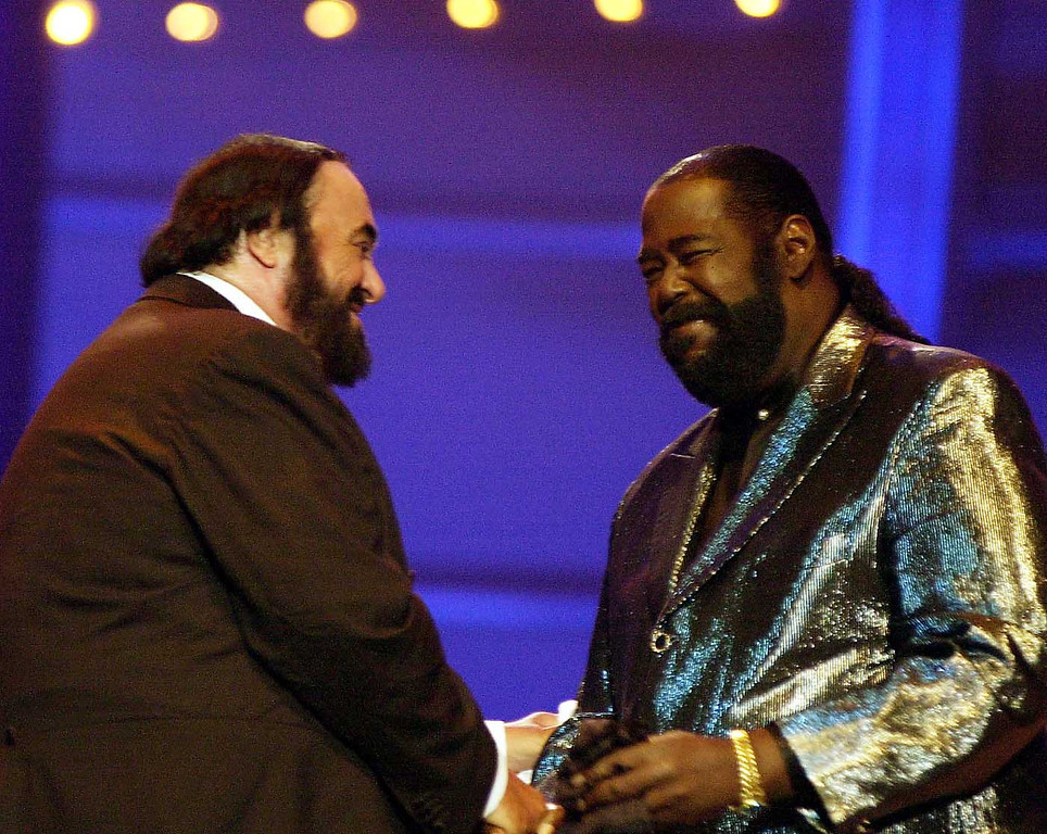 . Italian tenor Luciano Pavarotti shakes hands with U.S. singer  Barry White during the Pavarotti & friends 2001 annual charity concert at the Parco Novi Sad in Modena, Italy, Tuesday, May 29, 2001. (AP Photo/Luca Bruno)