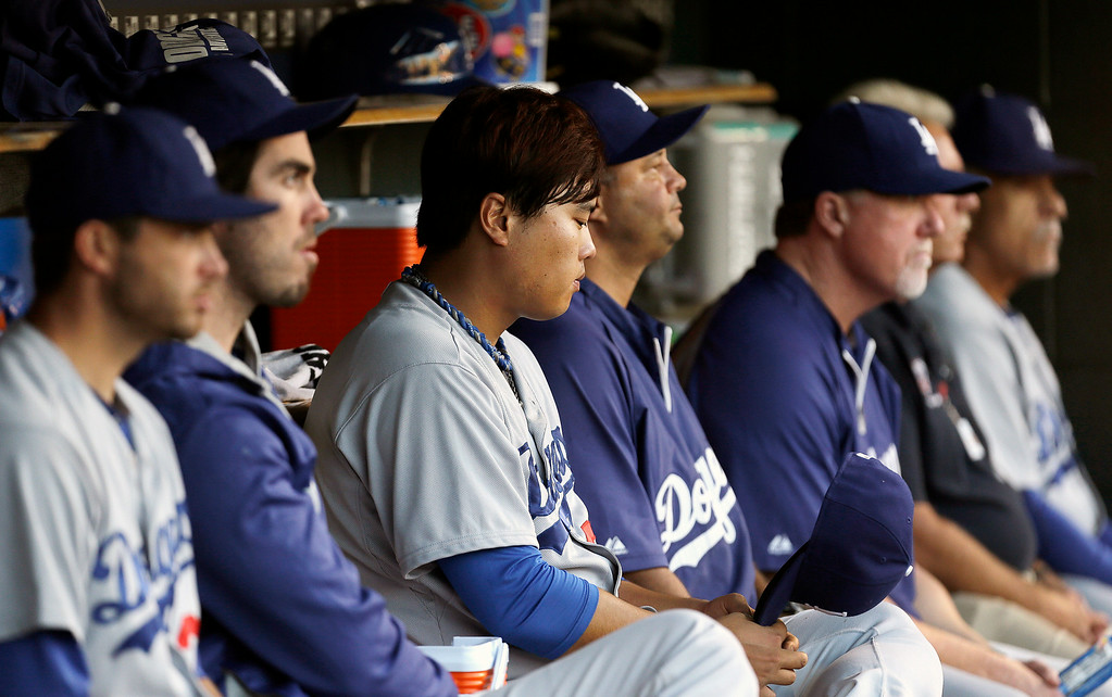. Los Angeles Dodgers pitcher Hyun-Jin Ryu, third from left, sits on the bench after being pulled against the Detroit Tigers in the third inning of a baseball game in Detroit, Tuesday, July 8, 2014. (AP Photo/Paul Sancya)