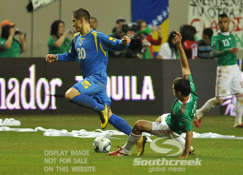 Bosnia-Herzegovina's Defender Muhamed Besic (#20) gets tripped up in Soccer action between Bosnia-Herzegovina and Mexico.  Mexico defeated Bosnia-Herzegovina 2-0 in the game at the Georgia Dome in Atlanta, GA.