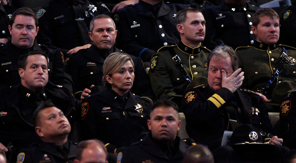 ". A tear is wiped away from one of the thousands of law enforcement officers gathered at the HP Paviilion memorial service for slain Santa Cruz police officers Sgt. ""Butch\"" Baker and Detective Elizabeth Butler on Thursday, March 7, 2013 in San Jose, Calif. The two were killed in an ambush in Santa Cruz last week. (Karl Mondon/Staff)"