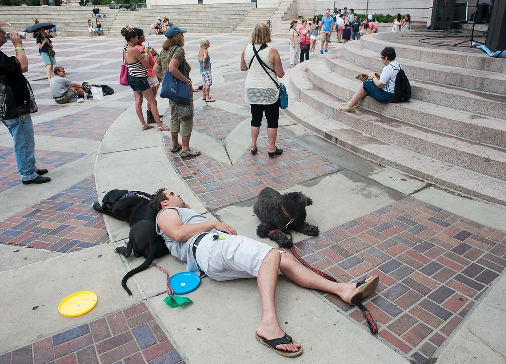 . Lyle Jackson lays with his dogs Derby (L), and Rowan (R), near a music stage area at Woof Fest! in downtown Denver, Colorado, Sunday, August 17, 2014. The free festival included two music stages, food trucks, and space for pets and their owners to play. ((Photo By Brenden Neville/Special to The Denver Post))