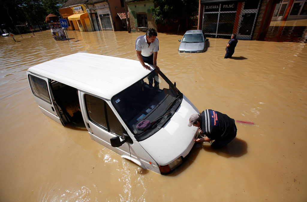 . Two men trying to restart their van stuck in a flooded street in Obrenovac, some 30 kilometers (18 miles) southwest of Belgrade, Serbia, Monday, May 19, 2014. Belgrade braced for a river surge Monday that threatened to inundate Serbia\'s main power plant and cause major power cuts in the crisis-stricken country as the Balkans struggle with the consequences of the worst flooding in southeastern Europe in more than a century. At least 35 people have died in Serbia and Bosnia in the five days of flooding caused by unprecedented torrential rain, laying waste to entire towns and villages and sending tens of thousands of people out of their homes, authorities said. (AP Photo/Darko Vojinovic)
