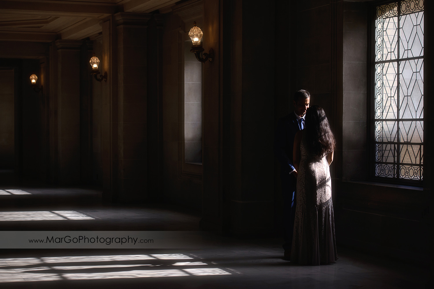 full body portrait of woman in beige dress and man in navy blue suit looking at each other in front of the window on the third floor of San Francisco City Hall