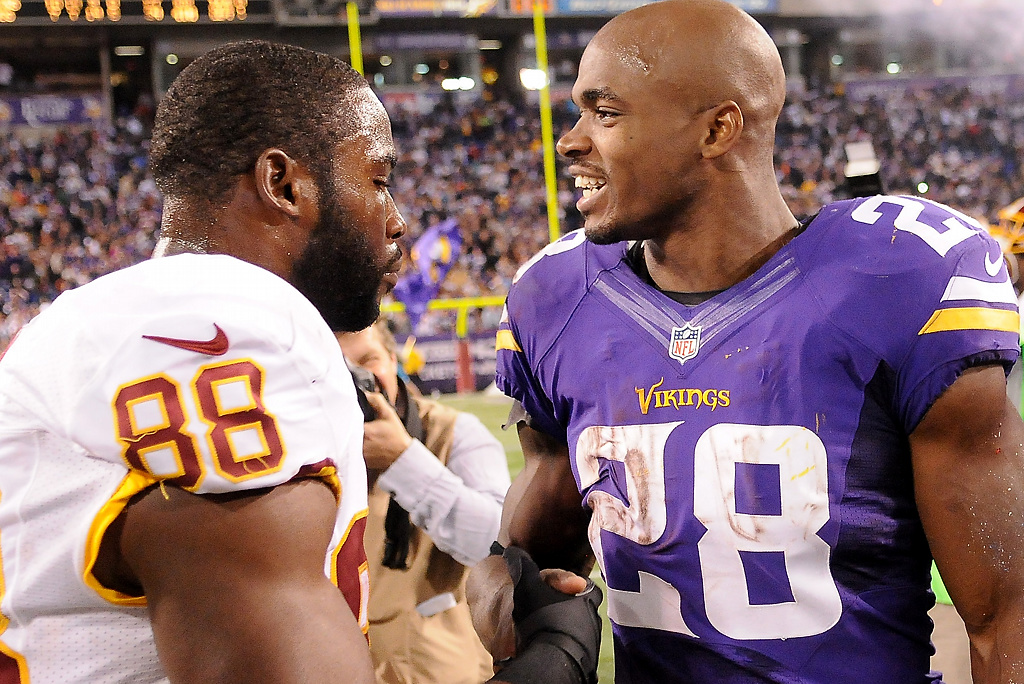 . Adrian Peterson and Washington wide receiver Pierre Garcon talk after the game. (Pioneer Press: John Autey)