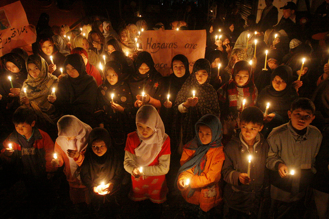 . Pakistani children hold candles at the site of Saturday\'s bombing, in Quetta, Pakistan, Thursday, Feb. 21, 2013. Pakistani Shiites buried their kin killed in a massive bombing last weekend in the southwestern city of Quetta but the funeral on Wednesday was marred by gunfire as both protesters and police fired into the air. (AP Photo/Arshad Butt)