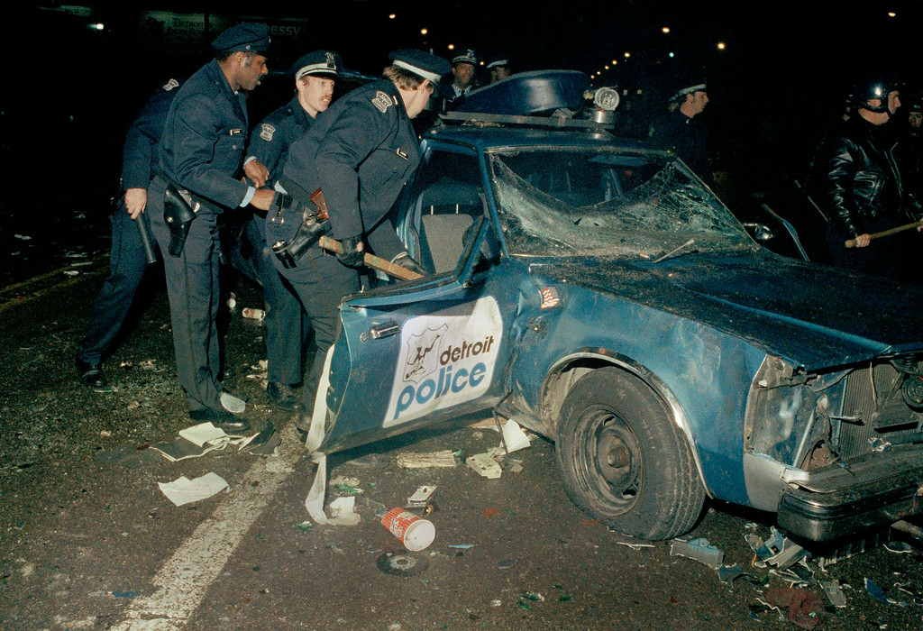 . Detroit police look at a  damaged police car after the World Series victory of the Detroit Tigers against the San Diego Padres on October 14, 1984 at Detroit.   (AP Photo)