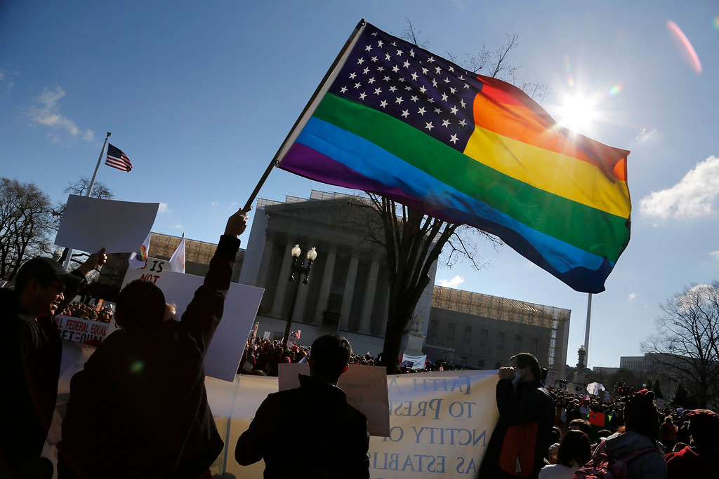 . Anti-Proposition 8 protesters wave a rainbow flag in front of the U.S. Supreme Court in Washington, March 26, 2013. Two members of the U.S. Supreme Court, both viewed as potential swing votes on the right of gay couples to marry, raised doubts about California\'s gay marriage ban on Tuesday as they questioned a lawyer defending the ban. REUTERS/Jonathan Ernst