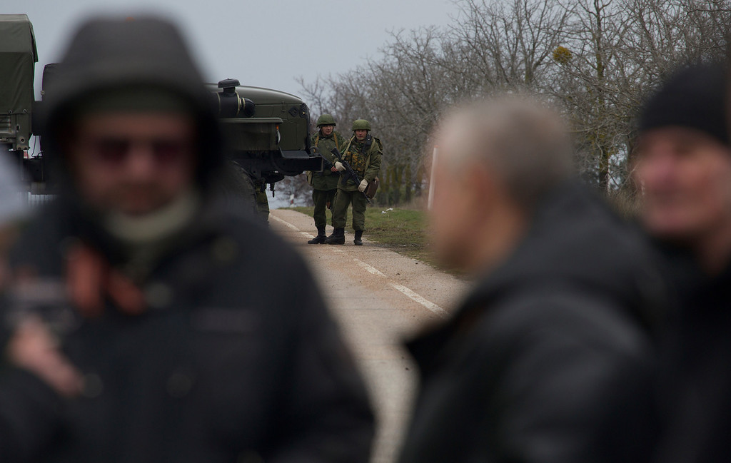 . Unidentified gunman block the road toward the military airport at the Black Sea port of Sevastopol in Crimea, Ukraine, Friday, Feb. 28, 2014 as local residents are seen foreground. (AP Photo/Ivan Sekretarev)