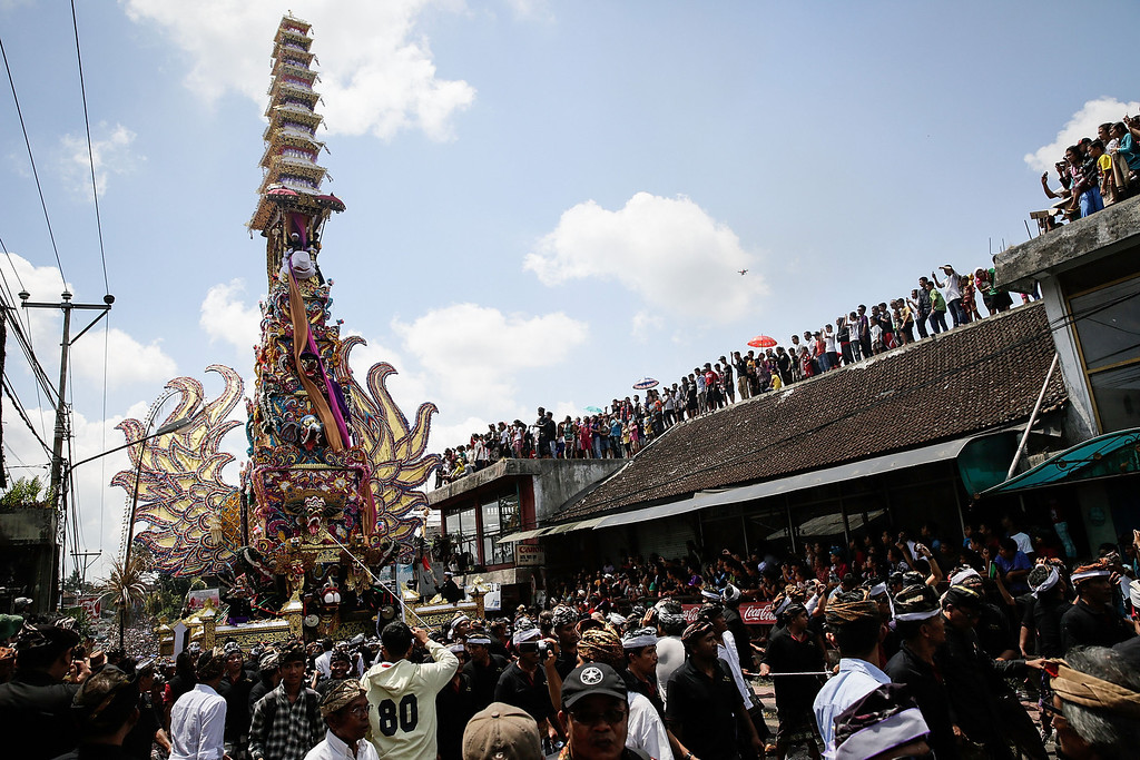 ". Ubud local carry the ""Bade\"" (body carrying tower) to the cemetery during the Royal cremation ceremony on November 1, 2013 in Ubud, Bali, Indonesia. (Photo by Agung Parameswara/Getty Images)"