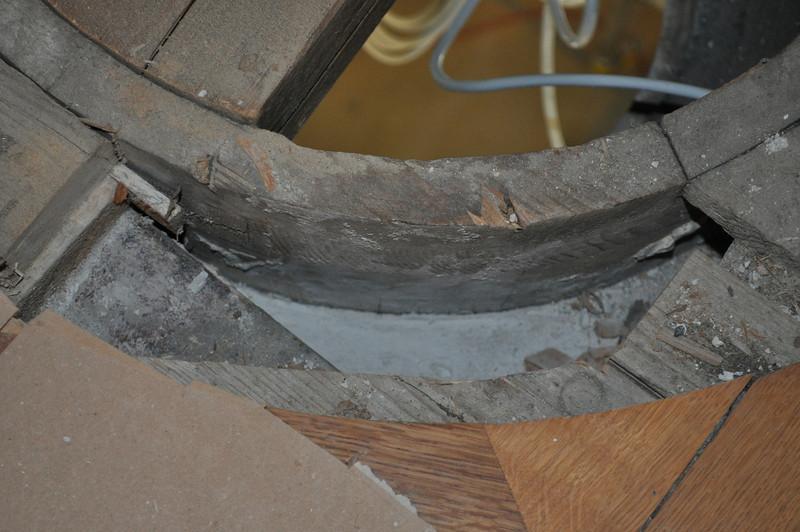 oberer Ausgang der Öffnung im grosen Deckendspiegel. Rundes Parkettelement entfernt.  Neben dem runden Holzelement verläuft ein Metallträger. Daran schliesst eine Betonplatte an. Da der Beton passgenau an das runde Holzelement führt, ist davon auszugehen, dass jenes vor dem Ausgiessen eingesetzt wurde. An dieser Stelle befand sich zwischen Betonplatte und Blindboden ein Stück Zeitung, datiert auf 1881. DSC_0052