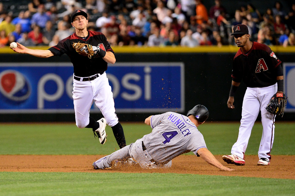 . Nick Ahmed #13 of the Arizona Diamondbacks turns the double play over the sliding Nick Hundley #4 of the Colorado Rockies in the second inning at Chase Field on April 30, 2016 in Phoenix, Arizona. (Photo by Jennifer Stewart/Getty Images)