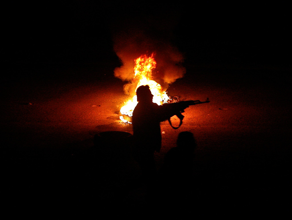. FILE - A Syrian rebel stands next to a flaming tire while firing at a Syrian army checkpoint in a suburb of Damascus, Syria, on Saturday, March 17, 2012. (AP Photo/File)