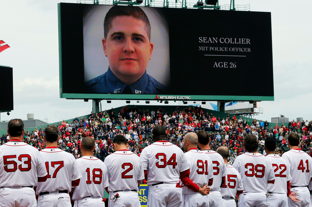 . The Boston Red Sox line up during a tribute to victims of the Boston Marathon bombing and its aftermath, as an image of Massachusetts Institute of Technology Police Officer Sean Collier is displayed on the scoreboard, before a baseball game against the Kansas City Royals in Boston, Saturday, April 20, 2013. (AP Photo/Michael Dwyer)