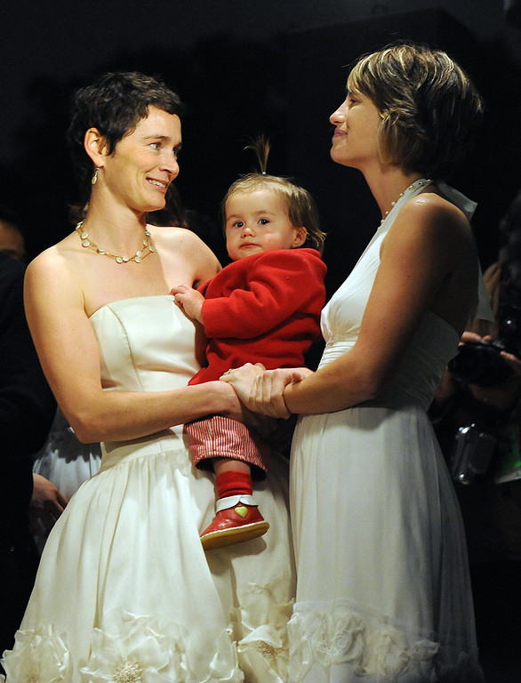 """. Kate Kuykendall (R) and her wife Tori Kuykendall (L) with their daughter Zadie -1, during a gay rights rally against the Proposition 8 measure at the El Pueblo de Los Angeles park on March 4, 2009.  California\'s top lawyer called for the result of a referendum effectively banning same-sex marriage to be quashed, ahead of the latest court-room showdown over the issue. Attorney General Jerry Brown said the ballot measure known as Proposition 8, which redefined marriage in California as a union between a man and a woman, should be invalidated because it \""""discriminates against same-sex couples.\""""      MARK RALSTON/AFP/Getty Images"""
