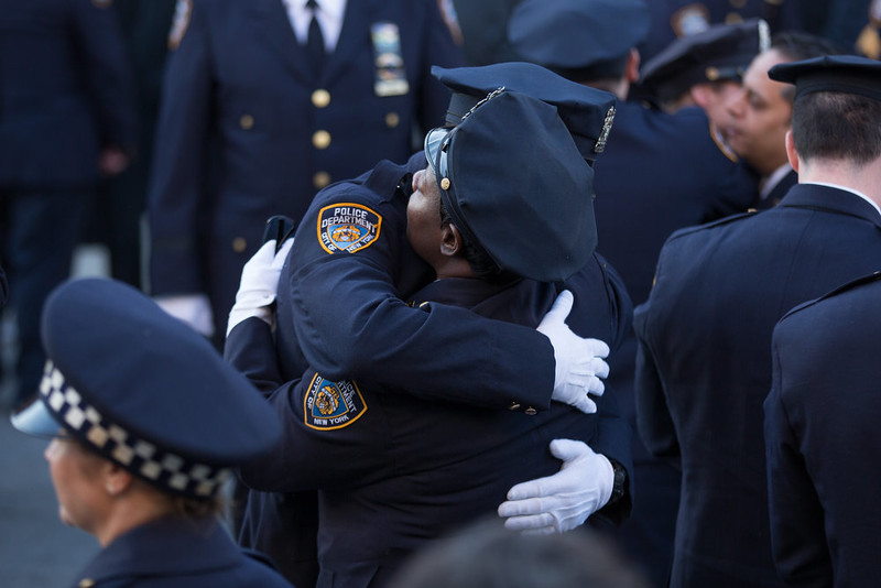 . New York Police Department (NYPD) officers embrace before the funeral of slain NYPD officer Rafael Ramos at the Christ Tabernacle Church December 27, 2014 in the Glenwood section of the Queens borough of New York City. Ramos was shot, along with Police Officer Wenjian Liu while sitting in their patrol car in an ambush attack in Brooklyn on December 20. Thousands of fellow officers, family, friends and Vice President Joseph Biden arrived at the church for the funeral.  (Photo by Kevin Hagen/Getty Images)