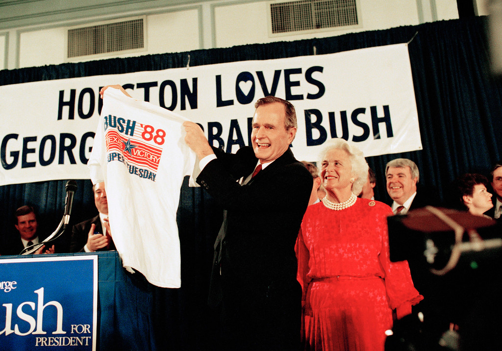 . Vice President George H W Bush holds up a Texas Victory shirt as wife, Barbara, watches during his victory celebration on March 8, 1988 in Houston. Bush won big in the super Tuesday primaries.(AP Photo/Ed Kolenovsky)
