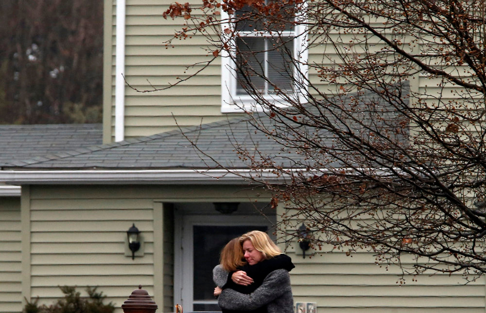 . People embrace near Honan Funeral Home, after attending the funeral service for six-year-old Jack Pinto in Newtown, Connecticut December 17, 2012. Pinto was one of 20 schoolchildren killed in the December 14 shootings at Sandy Hook Elementary School in Newtown.  REUTERS/Mike Segar