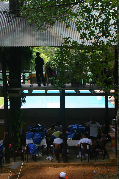 The Indian team under their shelter with the swimming pool in the background.