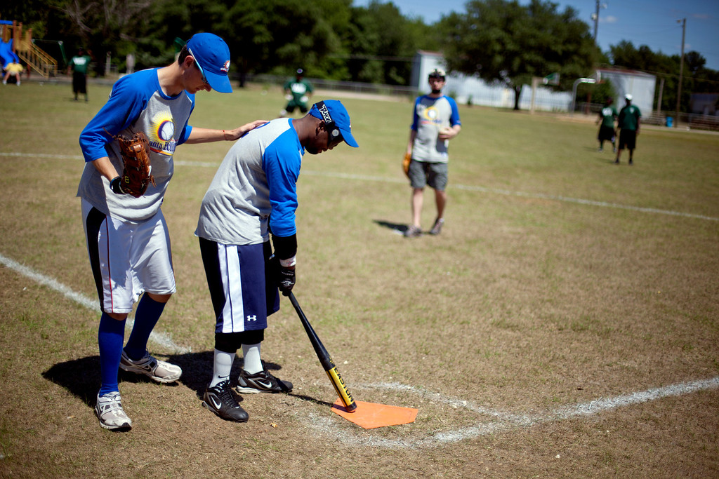 . Scean Atkinson, right, is helped with his position over the batters box with help from teammate Ben Poplin, during a blind baseball game in Albany, Ga. on May 5, 2012. For the players, the game is about much more than physical activity. Faced with their own personal challenges in their daily lives, hitting and catching a ball and running full speed in total darkness teaches them they can achieve what was thought unachievable. (AP Photo/David Goldman)