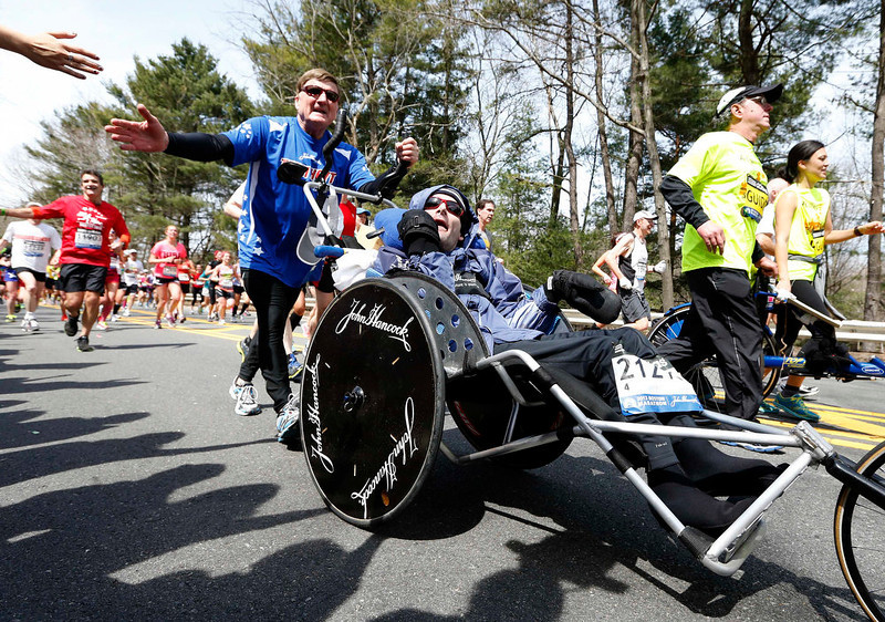 . Dick Hoyt, foreground left, pushes his son Rick on the Boston Marathon course in Wellesley, Mass., Monday, April 15, 2013. (AP Photo/Michael Dwyer)