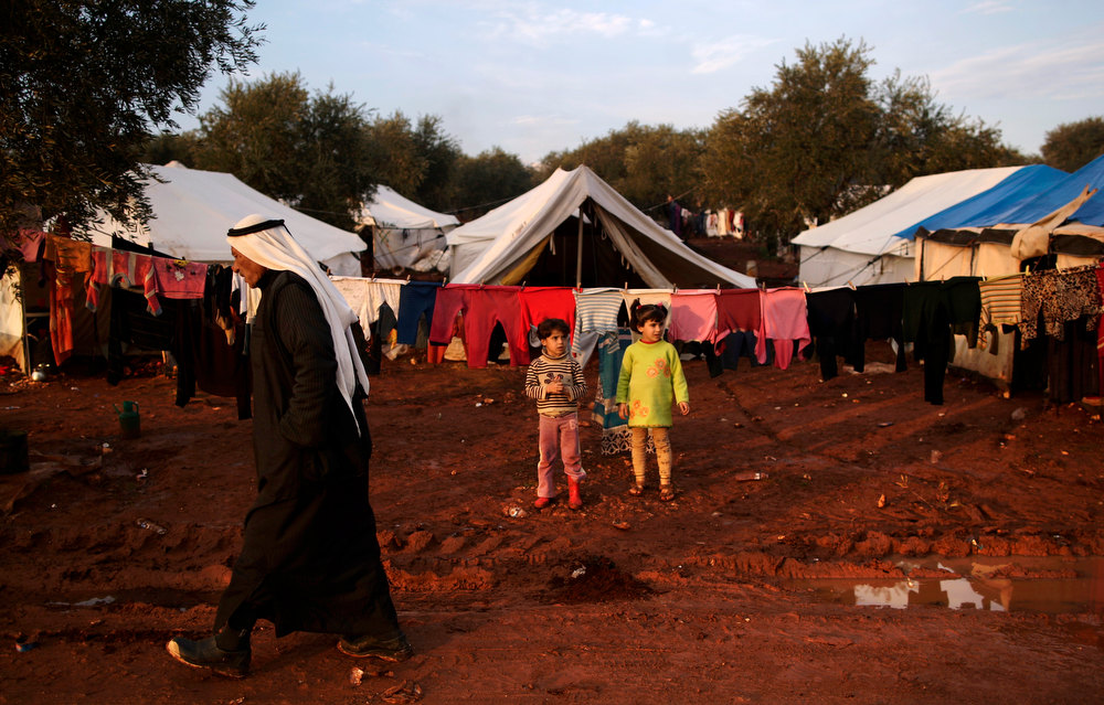 Description of . Syrian children, who fled their home with their families in Hama due to government airstrikes, stand next to their tent at a camp for displaced Syrians in the village of Atmeh, Syria, Thursday, Dec. 13, 2012. (AP Photo/Muhammed Muheisen)
