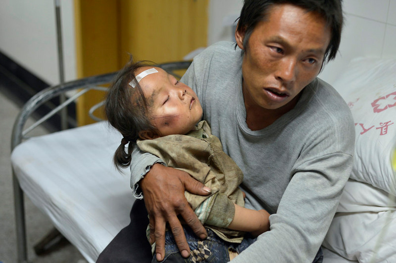 . A man holds an injured child receiving medical treatment at a hospital following an earthquake in Ludian county in southwest China\'s Yunnan province Monday, Aug. 4, 2014. A strong earthquake in southern China\'s Yunnan province toppled thousands of homes on Sunday, killing hundreds and injuring more than a thousand people. (AP Photo)