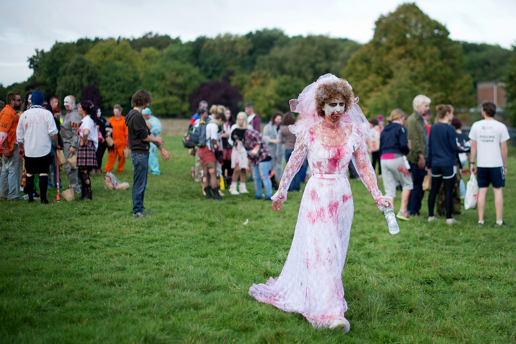 """. A volunteer zombie bride prepares to take part in one of Britain\'s biggest horror events, the \""""Zombie Evacuation Race\"""" at Carver Barracks near Saffron Walden, England, on October 5, 2013. The race sees thousands of participants attempt to complete a gruelling 5 kilometre cross-country run, while evading \""""zombies\"""", intent on snatching the three life-line strips hanging from every runner\'s waist.  Those who manage to get through with any strips remaining are named as survivors while those without take home an \""""infected\"""" badge.  LEON NEAL/AFP/Getty Images"""