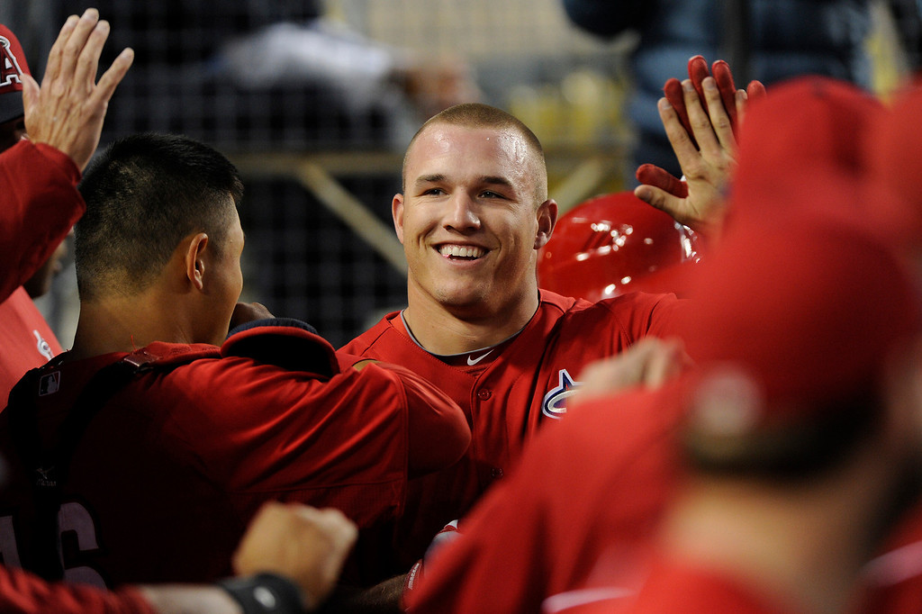 . The Angels\' Mike Trout is congratulated after scoring against the Dodgers from second on a hit by Albert Pujols in the first inning, Friday, March 29, 2013, at Dodger Stadium. (Michael Owen Baker/Staff Photographer)