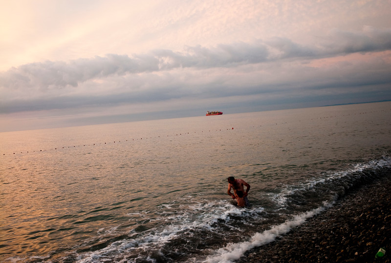 August 2011, Batumi, Georgia:  Man and a kid swim in the ocean, where an oil tanker can be seen in the background,  Batumi a port town known for its Oil tranport.  Since the flow of money has poured into Baku thanks to the Baku Tbilisi Ceyhan (BTC) oil pipeline, the Azeri capital has gone through intensive redevelopment.  However human rights organisations criticise the way in which inhabitants of old Baku have been forcefully evicted from homes earmarked for demolition with inadequate compensation.