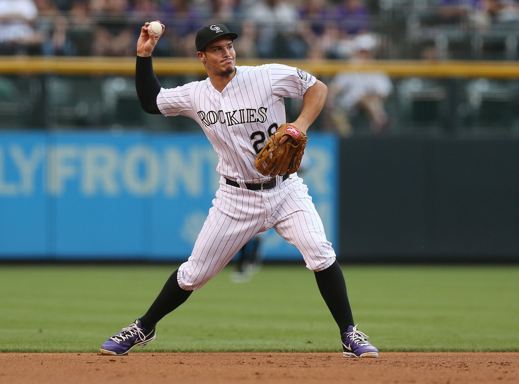 . Colorado Rockies third baseman Nolan Arenado throws to first base to put out Pittsburgh Pirates\' Andrew McCutchen in the first inning of a baseball game in Denver on Saturday, July 26, 2014. (AP Photo/David Zalubowski)
