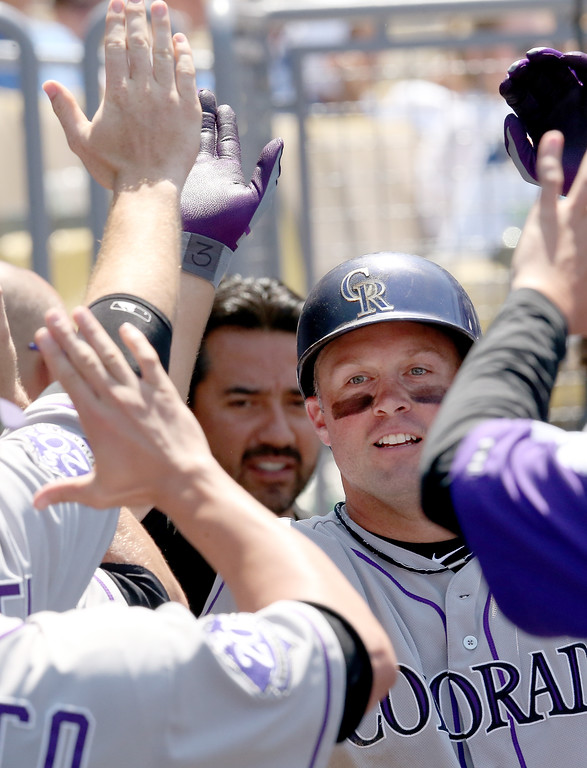 . Michael Cuddyer #3 of the Colorado Rockies celebrates in the dugout after hitting a two run home run in the fifth inning against the Los Angeles Dodgers at Dodger Stadium on July 14, 2013 in Los Angeles, California.  (Photo by Stephen Dunn/Getty Images)