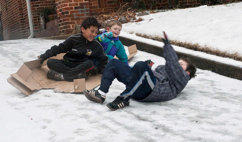 . John Staton, right, tumbles off a makeshift cardboard sled as his friends laugh, on Feb 12, 2014, in Decatur, Ga. Icy road conditions caused some businesses and schools to shut down in the greater metro Atlanta region. (AP Photo/ Ron Harris)