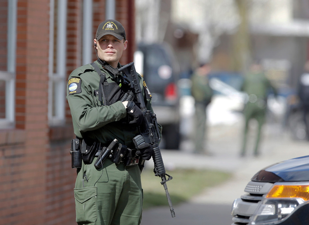 . A law enforcement officer stands on Main Street in Herkimer, N.Y., during the search for a suspect in two shootings that killed four and injured at least  two on, Wednesday, March 13, 2013.   (AP Photo/Mike Groll)