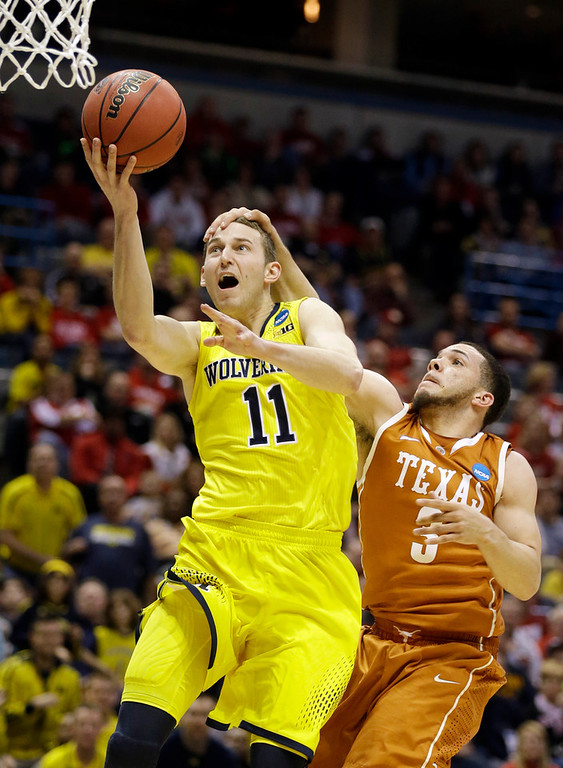. Michigan guard Nik Stauskas (11) is fouled by Texas guard Javan Felix (3) during the second half of a third-round game of the NCAA college basketball tournament Saturday, March 22, 2014, in Milwaukee. (AP Photo/Jeffrey Phelps)